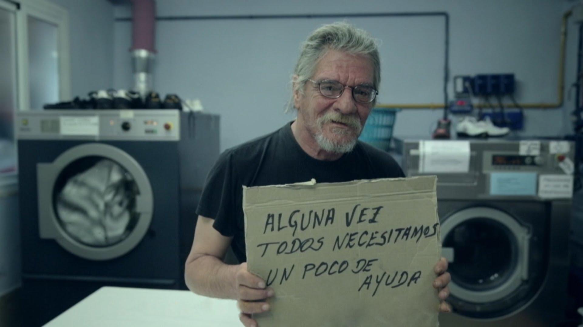 """Image illustrant l'un des sans-abris qui a participé au projet """"The Homeless Font"""" portant une pancarte avec son écriture."""